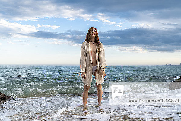 Rothaarige junge Frau steht vor dem Meer