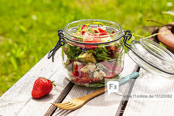 Strawberry avocado salad with feta  rocket and pine nuts in jar