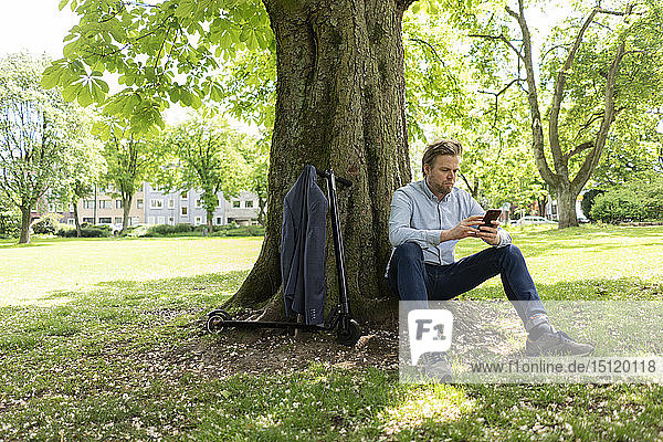 Geschäftsmann mit E-Scooter sitzt unter einem Baum im Stadtpark und benutzt ein Smartphone