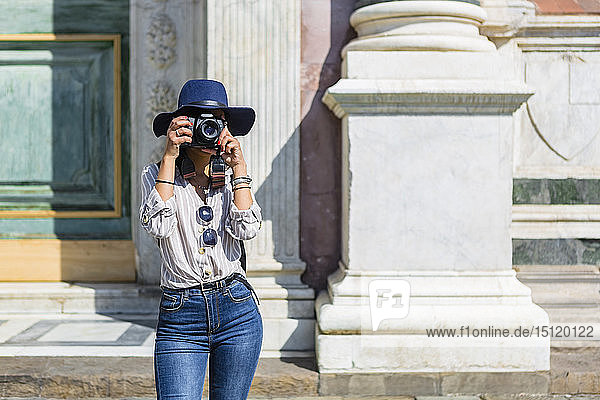 Italy,  Florence,  young tourist taking photograph with camera