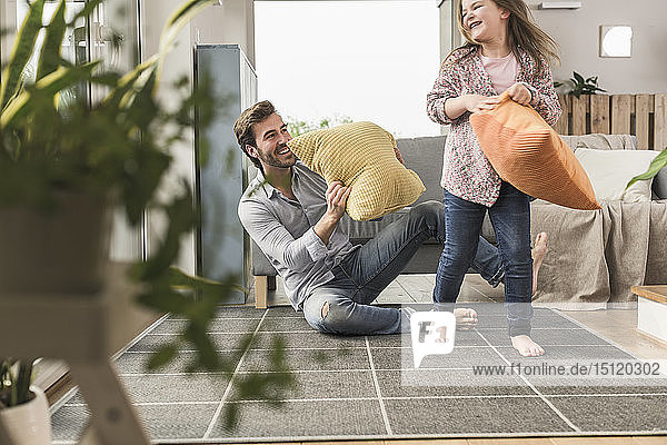 Young man and little girl having a pillow fight in the living room