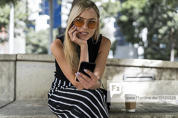 Portrait of blond young woman with cell phone sitting on a wall looking at distance