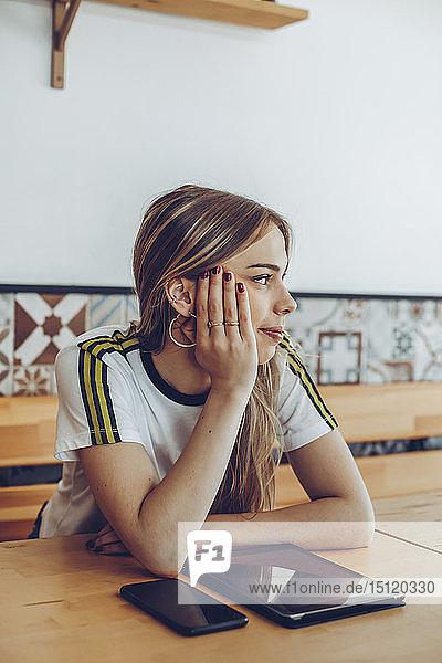 Junge Frau sitzt in einem Café und schaut weg