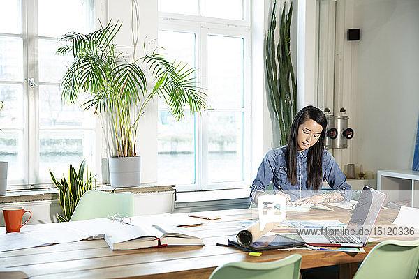 Frau  die in einem modernen Büro am Tisch arbeitet und Notizen macht
