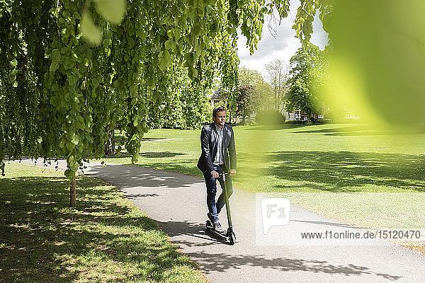 Geschäftsmann mit E-Scooter in einem Park