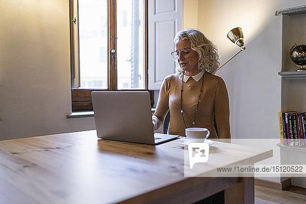 Reife Geschäftsfrau sitzt am Tisch mit einer Tasse Kaffee am Laptop