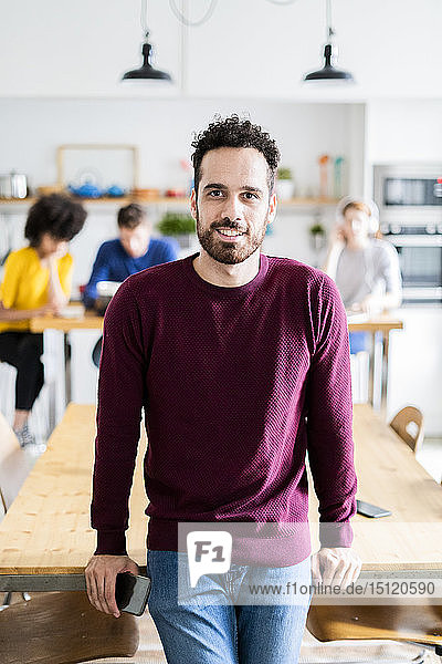 Portrait of smiling man at dining table at home with friends in background