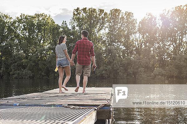 Junges Paar geht Hand in Hand auf einem Steg an einem abgelegenen See