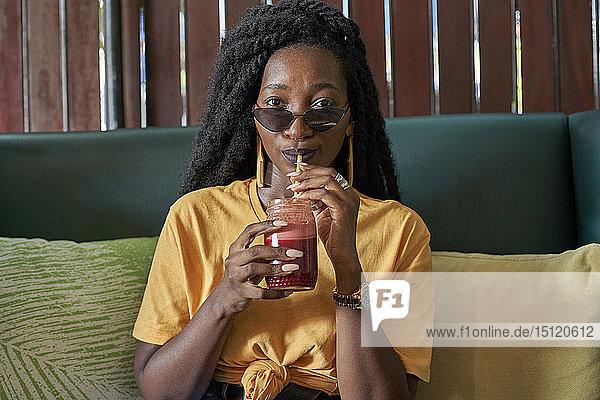 Junge Frau mit Dreadlocks  die in einem Café einen Smoothie trinkt