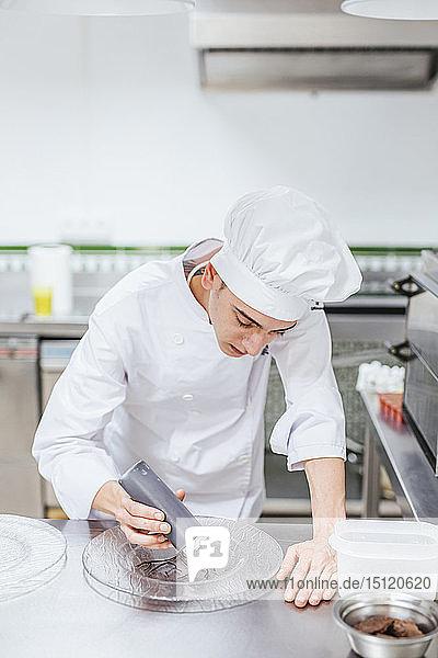 Junior-Chefkoch beim Vorbereiten eines Desserttellers