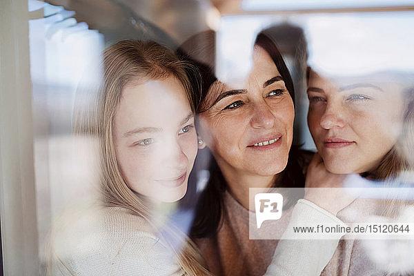 Besuchende Töchter  die ihre Mutter umarmen und am Fenster stehen