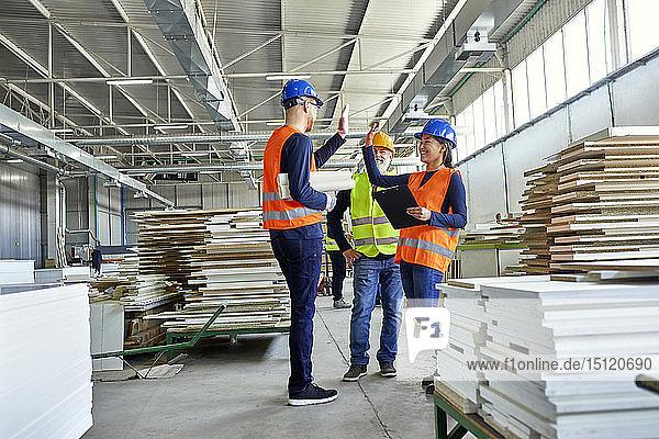 Glückliche Kollegen in der Arbeitsschutzkleidung in der Fabrik
