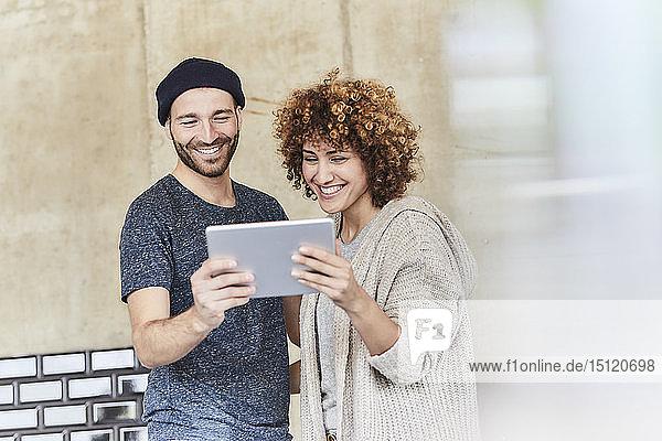 Glücklicher Mann und Frau teilen sich eine Tablette