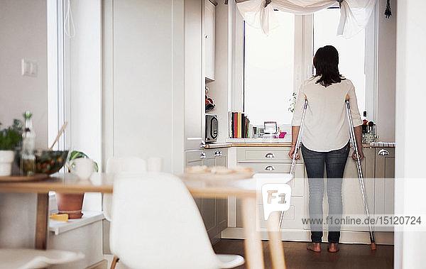 Reife Frau mit Krücken  allein zu Hause  schaut aus dem Fenster