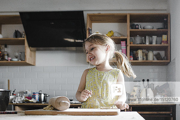 Happy little girl rolling out dough in the kitchen