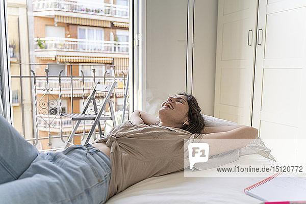 Glückliche junge Frau liegt mit geschlossenen Augen auf dem Bett