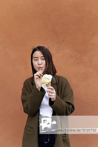 Young woman eating an ice cream cone at an orange wall