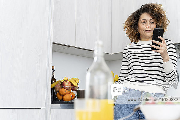 Woman standing in kitchen  using smartphone