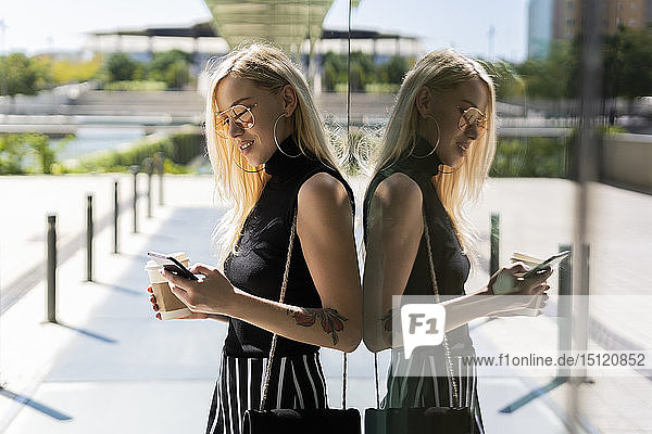 Blond young woman with coffee to go looking at cell phone