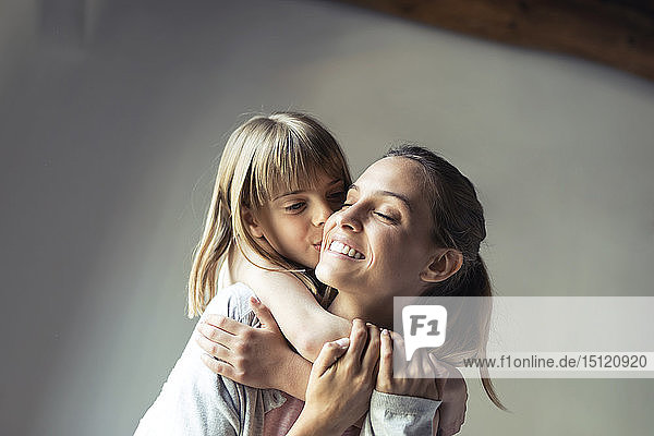 Mother and daughter playing at home  piggyback