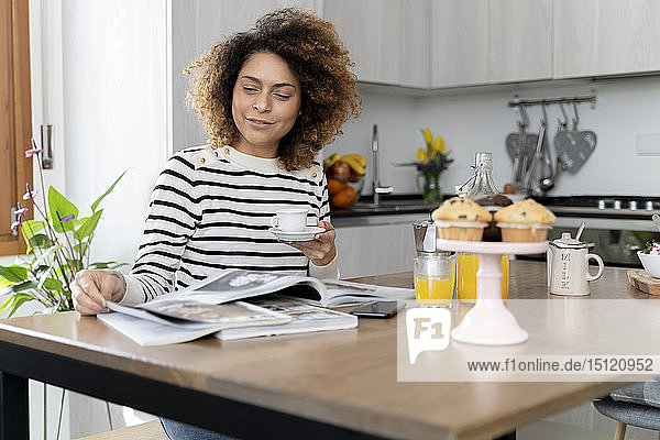 Woman sitting in kitchen  reading magazines and drinking coffee