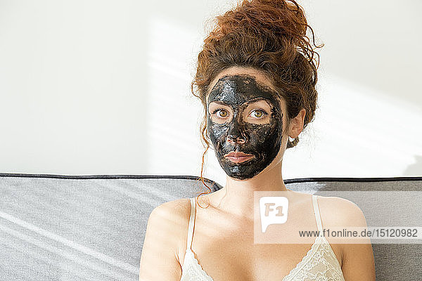 Portrait of young woman wearing facial mask at home