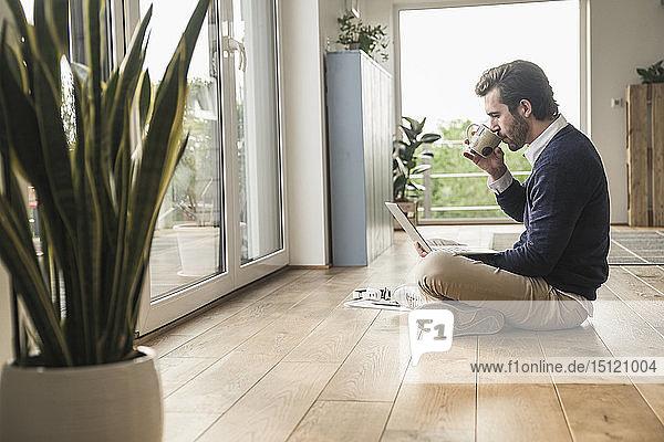 Junger Mann sitzt im Schneidersitz vor dem Fenster  benutzt Laptop  trinkt Kaffee