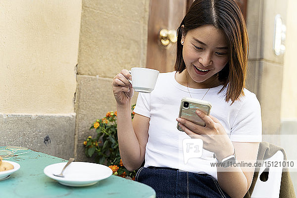 Italy  Florence  young woman using cell phone at an outdoor cafe