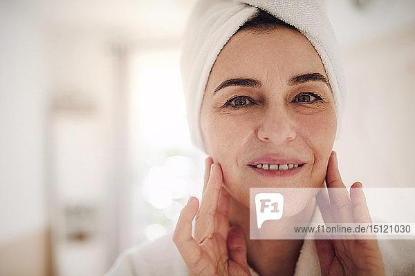 Porträt einer lächelnden reifen Frau in einem Badezimmer zu Hause