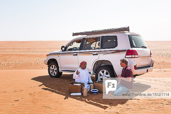 Tourist having a coffee break with his local driver in the desert  Wahiba Sands  Oman
