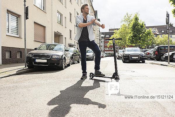 Mann steht mit E-Scooter auf der Straße