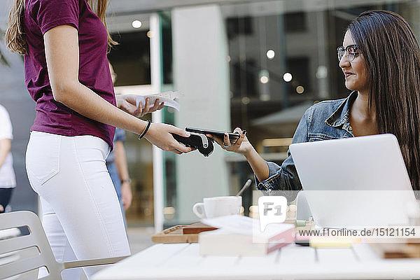 Junge Frau bezahlt bargeldlos mit Smartphone in einem Café