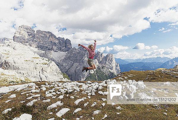 Wanderin beim Springen  Gebiet Tre Cime di Lavaredo  Naturpark Tre Cime  Unesco-Weltnaturerbe  Sextner Dolomiten  Italien