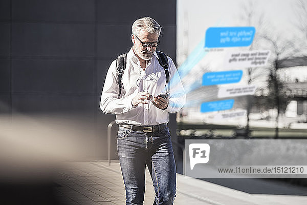 Mature businessman using cell phone for messaging in the city