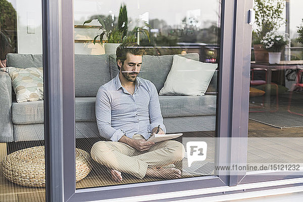 Young man sitting on ground  in front of window  taking notes