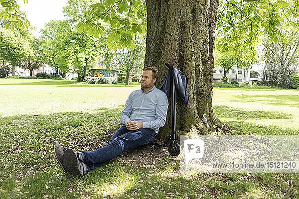 Geschäftsmann sitzt auf einem E-Scooter in einem Park und lehnt sich entspannt an einen Baumstamm