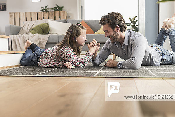 Young man and little girl lying on ground  arm wrestling
