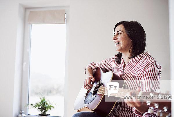 Glückliche reife Frau spielt zu Hause Gitarre
