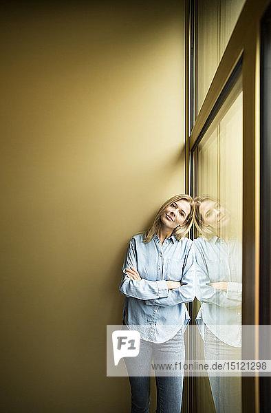 Geschäftsfrau steht an einem Fenster  schaut in die Kamera  AMS gekreuzt