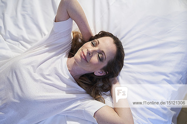 Smiling woman lying in bed with closed eyes