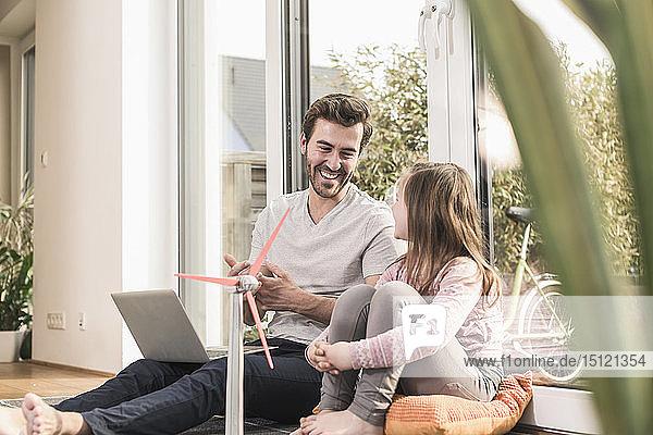 Junger Mann und kleines Mädchen spielen mit dem Modell einer Windkraftanlage