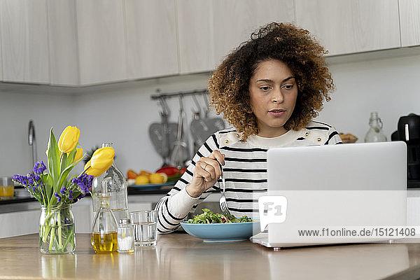 Frau benutzt Laptop  isst Salat zum Mittag