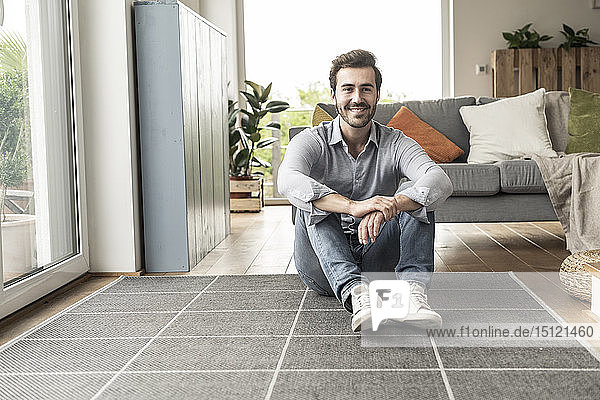 Confident young man sitting on floor of his livingroom