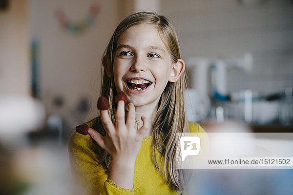 Glückliches Mädchen  das zu Hause am Küchentisch sitzt und mit Himbeeren spielt