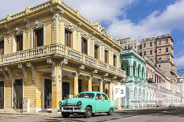 Vintage car driving in front of colonial buildings  Havana  Cuba