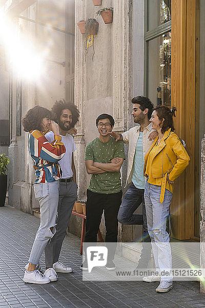 Fröhliche Gruppe von Freunden spricht in der Stadt