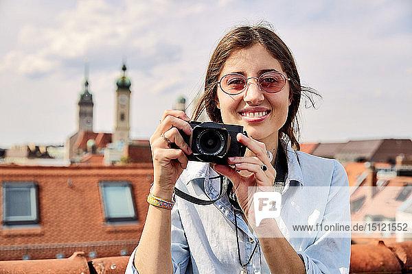 Junge lächelnde Frau beim Fotografieren