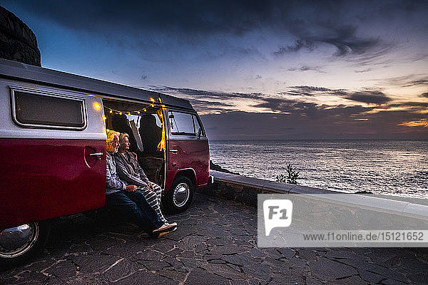 Senior couple traveling in a vintage van  watching sunset at the sea