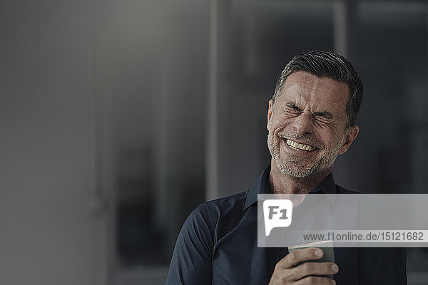 Happy mature businessman holding a cup