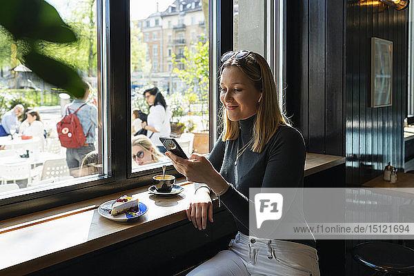 Lächelnde junge Frau in einem Café  die auf ein Smartphone schaut